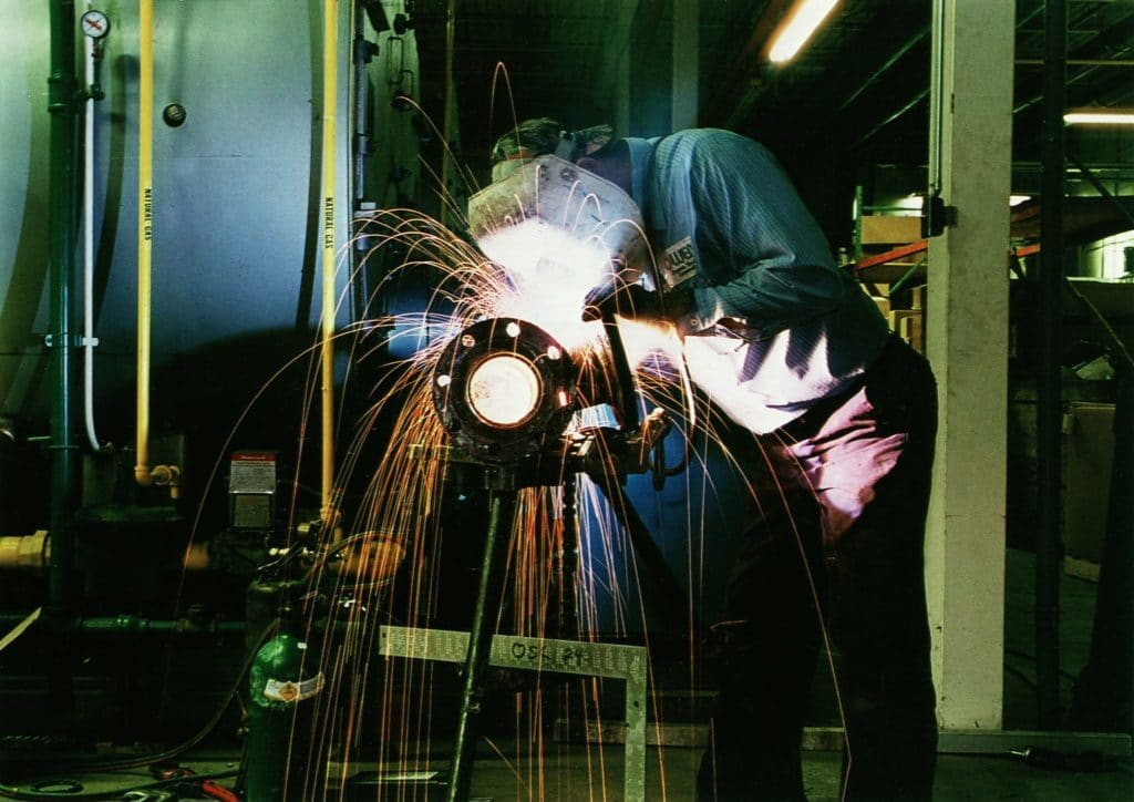 An Owens employee wearing a mask, welding a boiler pipe.