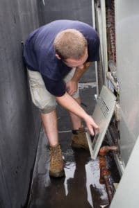An HVAC repair worker fixing a commercial unit.