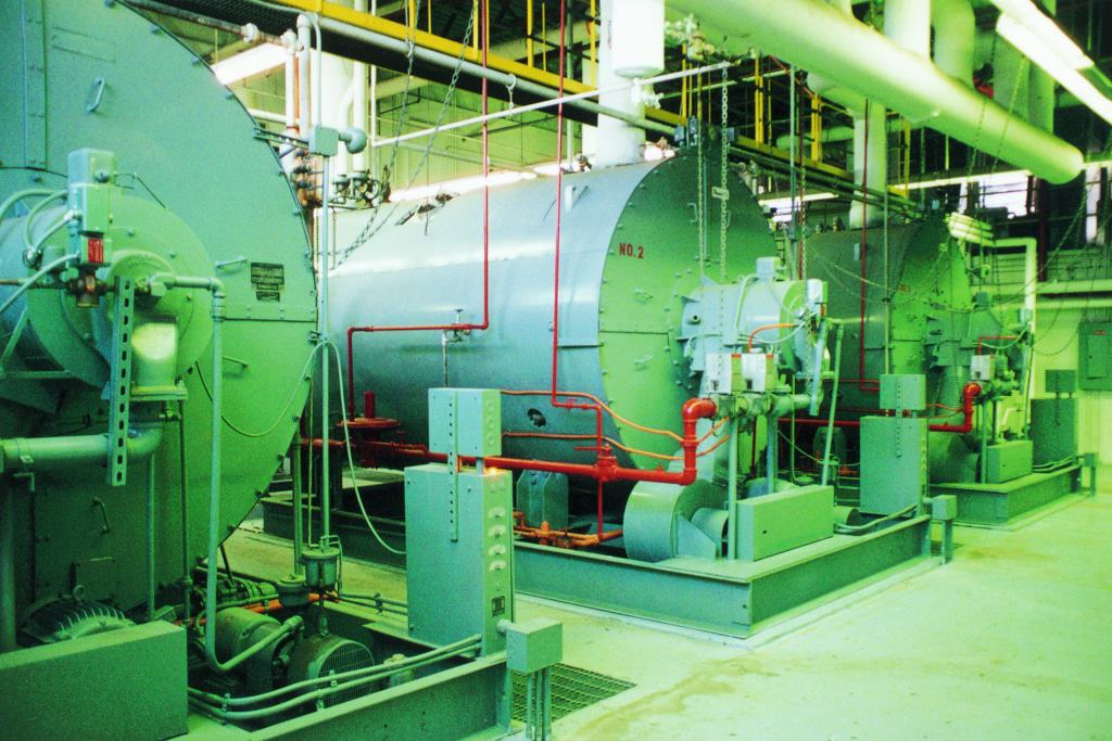 Three industrial boilers in a large utility room