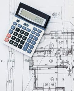 Close up of house blueprints with calculator