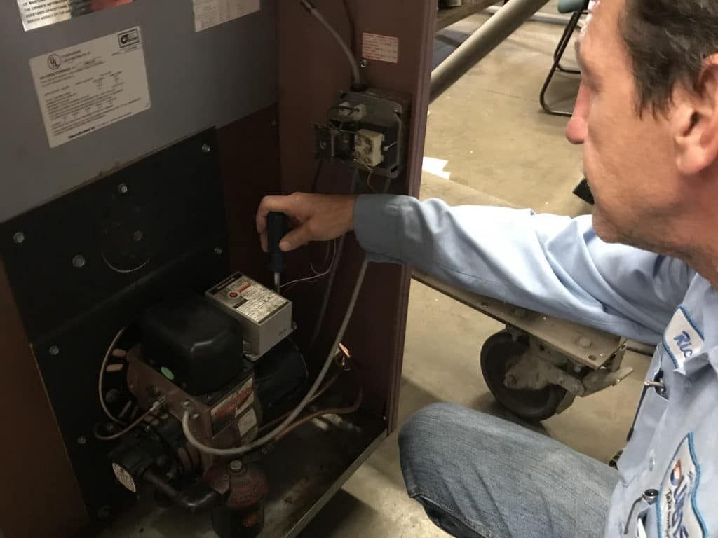 An Owens technician performing a repair on oil equipment