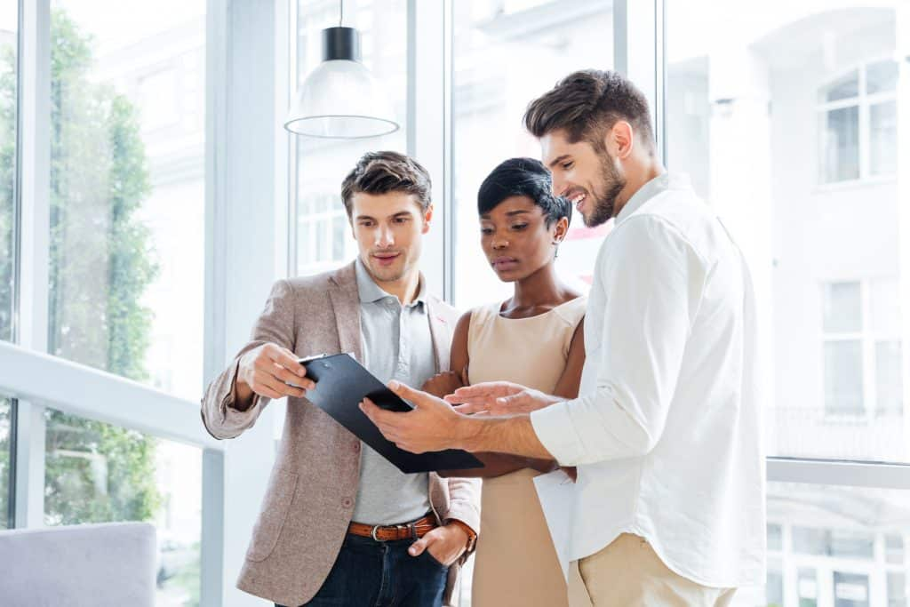 Three young people discussing business plan together in office