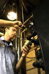 An Owens technician inspecting a boiler.