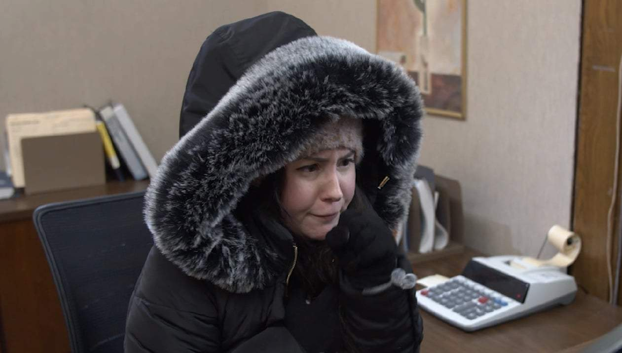 A woman wearing a parka while trying to work in an office.