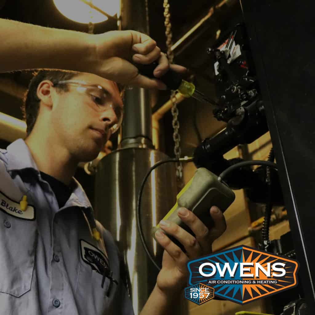 A picture of an Owens tech investigating equipment.
